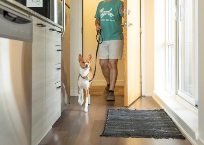dog walker coming home with dog
