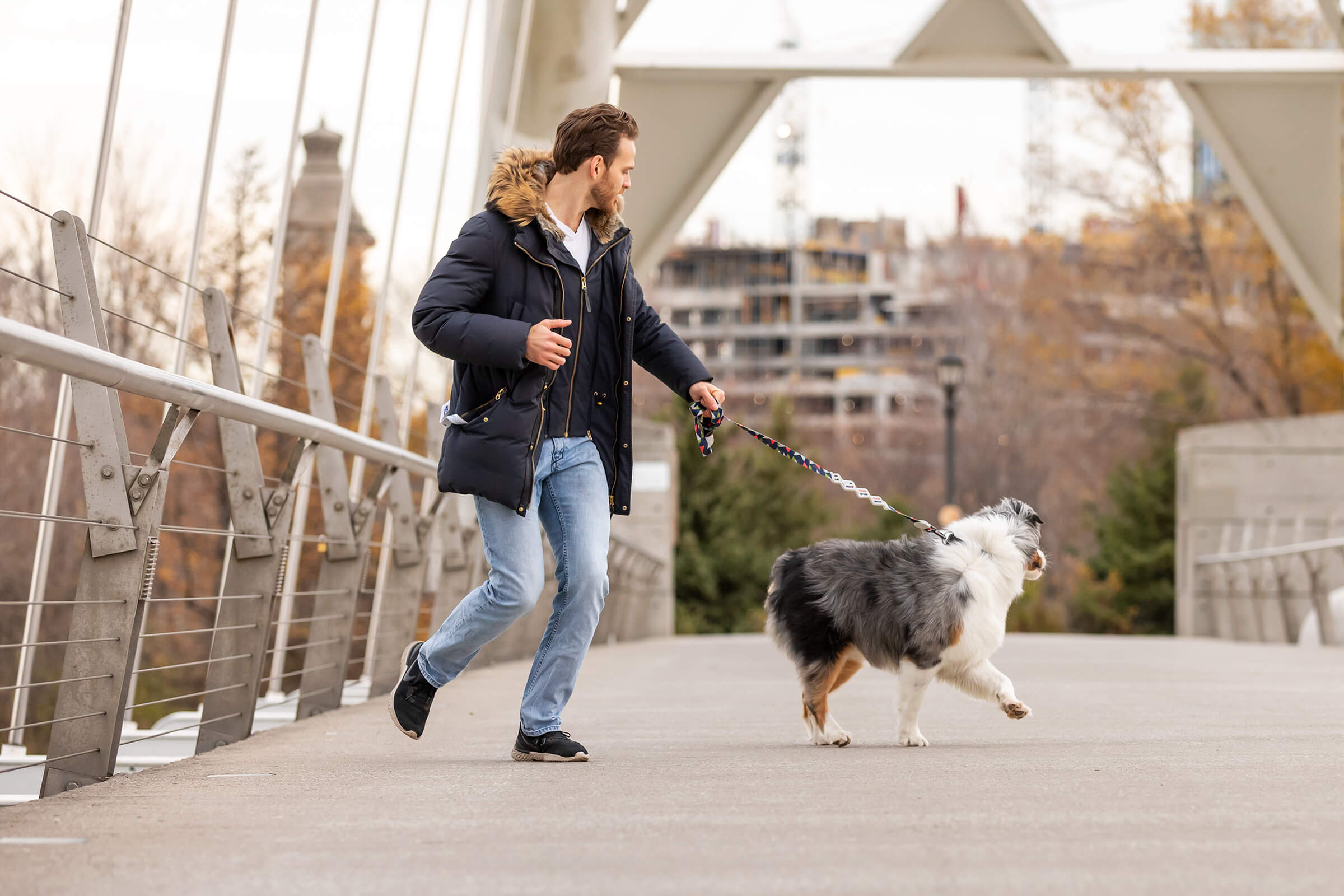man with dog running on bridge for commercial branding shoot